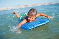 Pojken har gyckel med surfingbrädan Arkivfoton