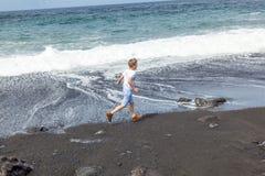 Pojken har gyckel på den svarta stranden royaltyfri foto