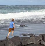 Pojken har gyckel på den svarta vulkaniska stranden Fotografering för Bildbyråer
