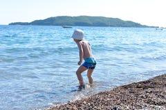 Pojken har gyckel på en strand som spelar i havet Arkivbilder