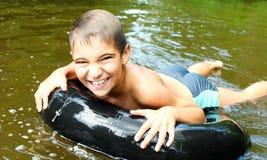 Pojken har gyckel på rör i floden fotografering för bildbyråer
