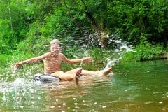 Pojken har gyckel på rör i floden arkivbild