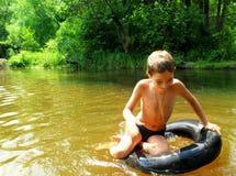 Pojken har gyckel på rör i floden royaltyfri fotografi