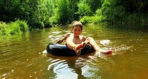 Pojken har gyckel på rör i floden royaltyfri bild