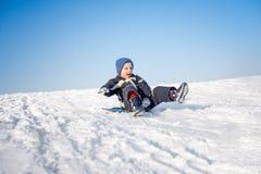 Pojken har gyckel på snö Royaltyfri Foto
