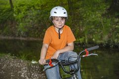 Pojken har gyckel som vilar på hans bmxcykel arkivfoton