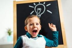 Pojken har idé med lightbulben som dras på den svart tavlan Royaltyfri Foto