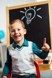 Pojken har idé med lightbulben som dras på den svart tavlan Fotografering för Bildbyråer
