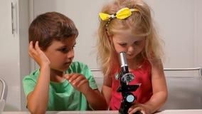Pojken hjälper en flickablick till och med ett mikroskop stock video