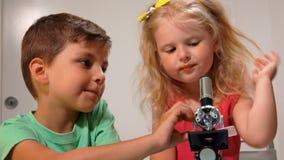 Pojken hjälper en flickablick till och med ett mikroskop lager videofilmer