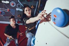 Pojken hjälper flickan att klättra väggen royaltyfria foton