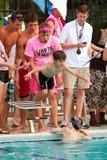 pojken hoppar av liten simmare för plattformsracerelay arkivfoto