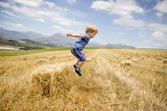Pojken hoppar från en Hay Stack i en Sunny Field Royaltyfri Fotografi