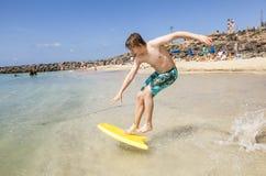 Pojken hoppar in i havet med hans boogiebräde Arkivbild