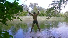 Pojken hoppar till floden från pir lager videofilmer