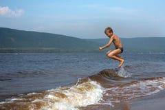 Pojken hoppar ?ver v?gorna p? stranden solig dagsommar royaltyfri fotografi