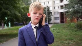 Pojken i affärsdräkt talar på en mobiltelefon i parkerar och Främre sikt, framsida