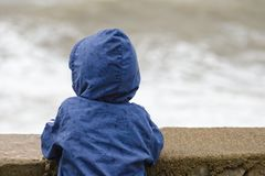 Pojken i blått omslag med huvställningar med hans baksida mot pir mot bakgrunden av havet vinkar Arkivbilder