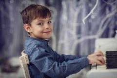 Pojken i den blåa skjortan som spelar på ett vitt piano Arkivbild