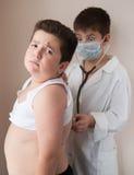 Pojken i dräkt av doktorn kontrollerar hjärtslag av den feta pojken med stetoskopet arkivbild