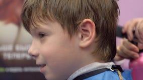 Pojken i en barberare shoppar för en frisyr, framsidanärbilden, sidosikt lager videofilmer