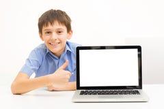 Pojken i en blå skjorta använder en bärbar dator som inomhus sitter på en tabell Royaltyfri Bild