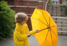 Pojken i en ljus gul regnrock öppnar ett paraply under arain Arkivfoto