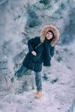 Pojken i ett omslag med en huv i ett snöig parkerar Royaltyfri Foto