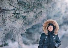 Pojken i ett omslag med en huv i ett snöig parkerar Arkivbild