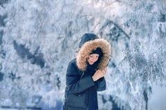 Pojken i ett omslag med en huv i ett snöig parkerar Arkivfoton