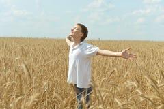 Pojken i fält tycker om naturen Arkivfoton