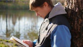 Pojken i höst parkerar nära sjön som läser en bok härlig liggande för höst Skolutbildning Royaltyfria Bilder