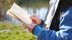 Pojken i höst parkerar nära sjön som läser en bok härlig liggande för höst Skolutbildning Arkivbilder