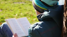 Pojken i höst parkerar nära sjön som läser en bok härlig liggande för höst Skolutbildning arkivfilmer