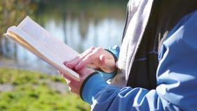 Pojken i höst parkerar nära sjön som läser en bok härlig liggande för höst Skolutbildning stock video