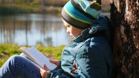 Pojken i höst parkerar nära sjön som läser en bok härlig liggande för höst Skolutbildning Royaltyfri Fotografi