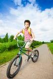Pojken i hjälm rider hans cykel längs vägen Royaltyfri Fotografi