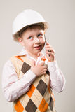 Pojken i konstruktionshjälmen som talar på telefonen Arkivfoto