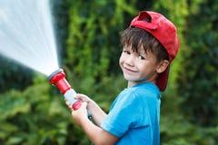 Pojken i lock häller utomhus- vatten royaltyfri foto