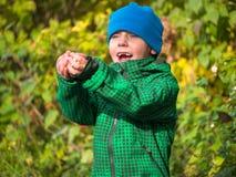 Pojken i omslag och lock sträckte ut hans armar och ropa Arkivfoto