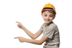 Pojken i orange konstruktionshjälm visar pekfingrar åt sidan Stående Isolat på vitbakgrund royaltyfria foton