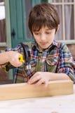 Pojken i rutigt bulta för skjorta spikar i träplanka royaltyfri foto