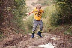 Pojken i stövlar hoppar in i pölen Royaltyfri Bild