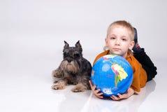 Pojken, jordklot och en hund Royaltyfria Bilder