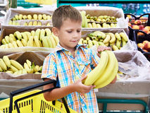 Pojken köper bananer i lager Royaltyfria Foton