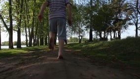 Pojken kör längs skogvägen barfota, begrepp av frihet och lycka lager videofilmer