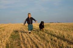 Pojken kör med hunden Royaltyfria Bilder