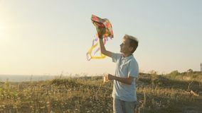 Pojken kör och försöker att lansera en drake i himlen i en stark vind stock video