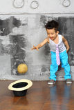 Pojken kastar en boll i en hatt royaltyfri fotografi