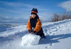 pojken kastar snöboll Arkivfoto